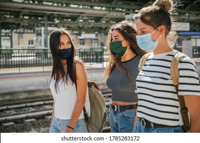 Three young friends women at the station walking and waiting train for their trip in summer with face mask for protection by infection from Corona virus, Covid-19 - Millennials having fun together