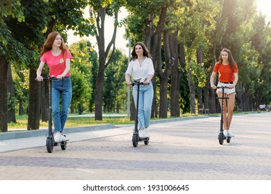 Three young girl friends on the electro scooters having fun in city street at summer sunny day. Outdoor portrait of three friends girl riding electric kick scooter in the park.