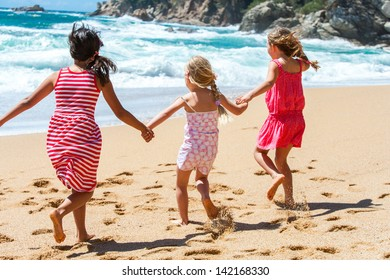 Three young girlfriends running on beach holding hands.