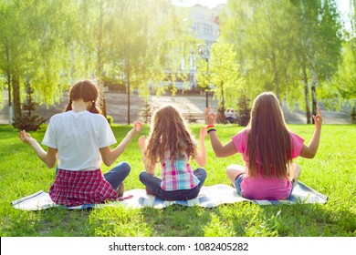 Three young girls doing yoga