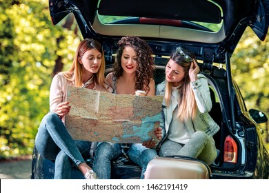 Three young girls going on vacation with car. They are sitting in car trunk and holding map.