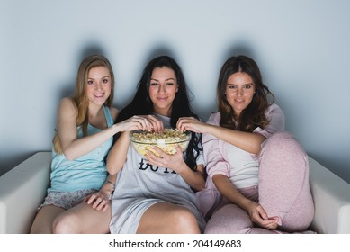 Three young girls looking at tv show