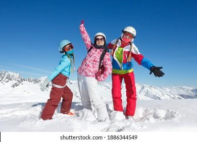Trois jeunes filles en vacances d'hiver dans les alpes françaises posent dans la neige avec veste et casque de ski