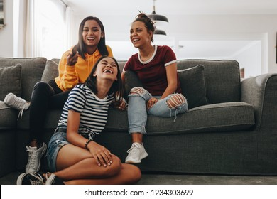 Three young girls sitting together at home watching television and laughing. Teenage girls at a sleepover having fun watching TV sitting in the living room.