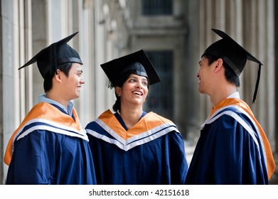 Three young graduates wearing graduation attire chatting in a hallway