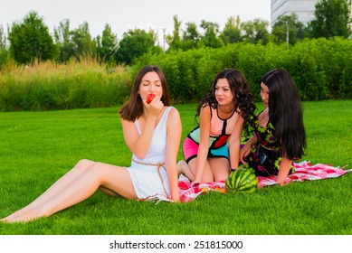 Three  young happy girlfriends picnicking in the park  on green grass  and enjoying  fruit