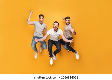 Three young happy men jumping together isolated over yellow background