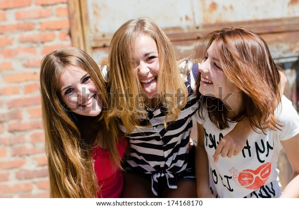 Three young happy smiling & looking at camera teenage girl friends have fun in city outdoors