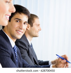 Three young happy smiling successful businesspeople at meeting, presentation or conference. Success in business and teamwork concept.