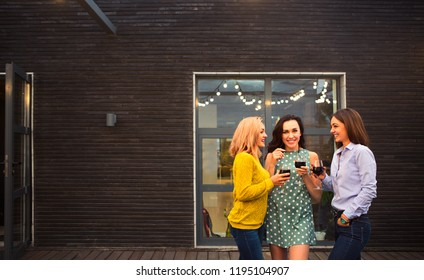 Three young happy woman laughing, drinking red wine, having fun. Party and friendship concept.