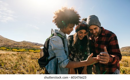 Three young hikers looking at pictures on mobile phone. Young people hiking in countryside.