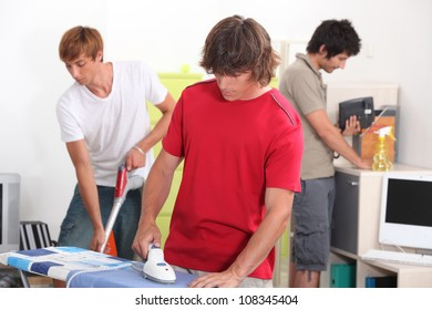 Three young male house-mates cleaning