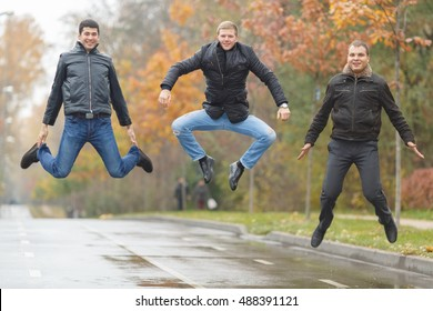 Three young men in black jackets jumping for fun in alley in park