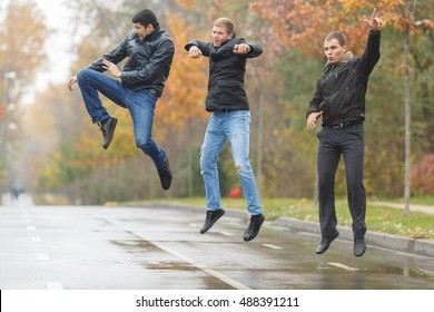 Three young men in black jackets jumping for joy in alley in park