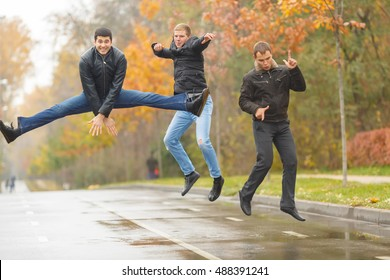 Three young men in black jackets jumping for merry-making in alley in park