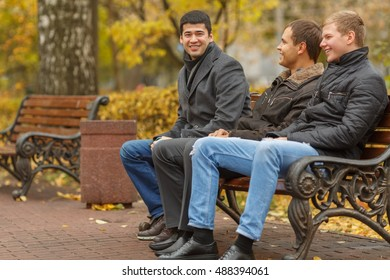Three young men in black jackets sitting on park bench, talk and smile, side view