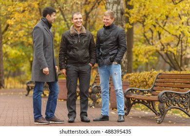 Three young men in black jackets standing near park bench, talk and smile