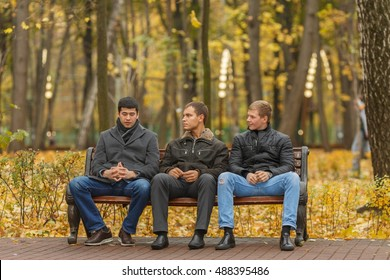 Three young men in black jackets sitting on bench in park, one says, two listen to him