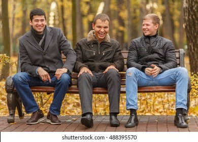 Three young men in black jackets sitting on park bench, talk and smile