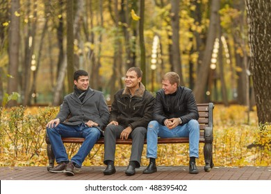 Three young men in black outerwear sitting on park bench and talk