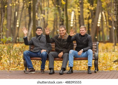 Three young men in black outerwear sitting on bench in park, waving palm and smiling