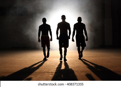 Three young men boxing workout in an old building