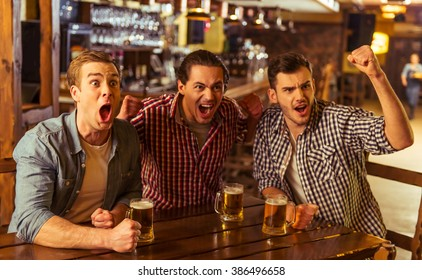 Three young men in casual clothes are cheering for football and holding glasses of beer while sitting in pub