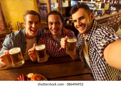 Three young men in casual clothes are smiling, taking selfie and drinking beer while sitting in pub