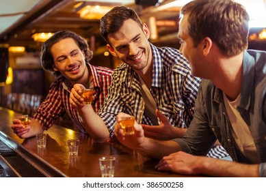 Three young men in casual clothes are talking, laughing and drinking while sitting at bar counter in pub