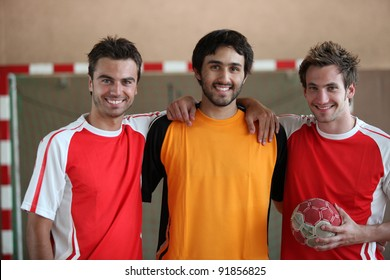 Three young men indoors with hand ball