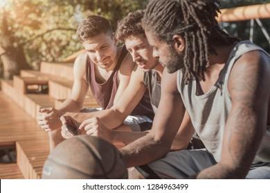 Three young men sitting on an outdoor wooden basketball court bleachers.