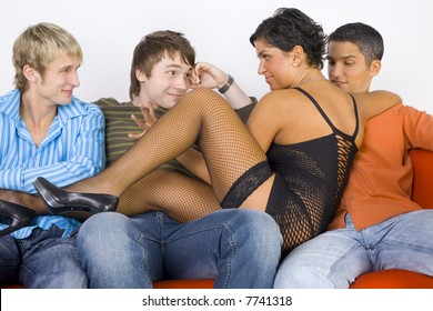 Three young men sitting on orange couch with stripteaser. She is sitting between men and looking at one