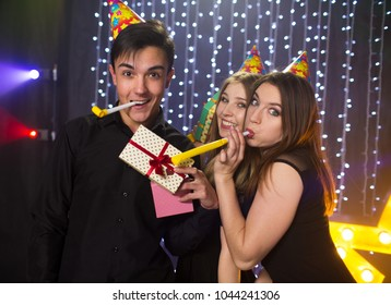 Three young men and two women have fun in a nightclub at a party