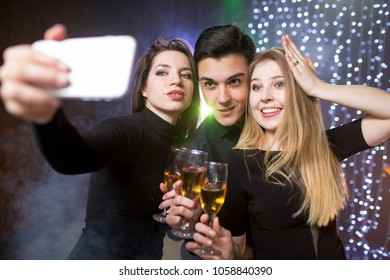 Three young men and two women  with glass champagne make selfie photo on smartphone celebrate a birthday have fun in a nightclub at a party