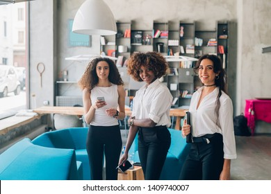 three young multicultural businesswomen standing with smartphone in modern loft – inventive, freelance, dedication