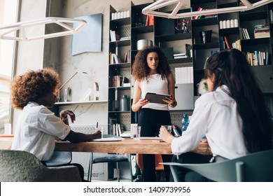 three young multicultural businesswomen talking about project in coworking office– resourceful, emancipation, dedication