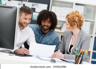 Three young multiethnic coworkers discussing paperwork as they sit together at a desk smiling as they input and share their ideas