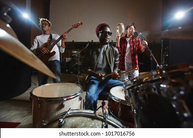 Three young musicians playing musical instruments and performing songs in studio of records