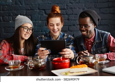 Three young people of different races having video call to their common friend, using free wireless internet connection on touch pad, having happy cheerful looks. Modern technology and communication