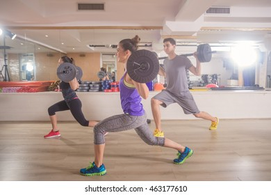Three young people gym lunge weights bar women man