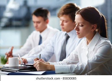 Three young people making notes at lecture