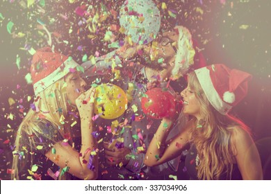 Three young people at New Year's Eve party on midnight blowing colorful balloons and having fun