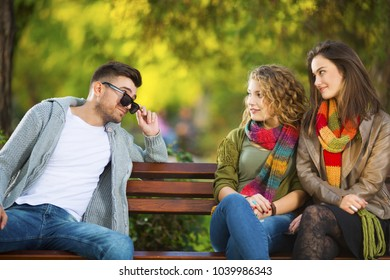 Three young people on a bench flirting