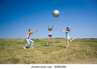 three young people pay with big ball
