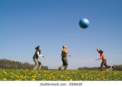 Three young people playing with big ball on the spring meadow