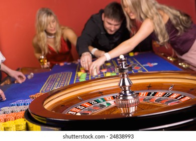 Three young people playing roulette, casino