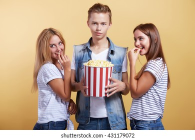 three young people with popcorn