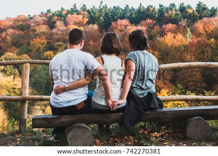 Three young people are sitting on a bench, a guy cheating on his girlfriend