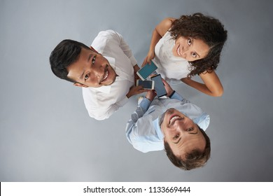Three young people with smartphones smiling to camera isolated on gray background above top view