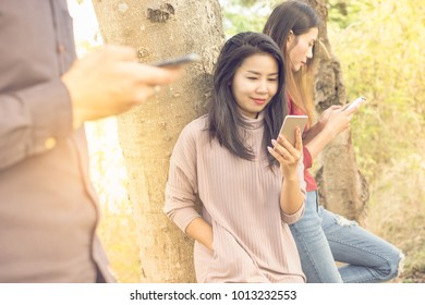 three young people standing  in a park socially ignoring each other because of their using their smartphones , which conveys the concepts of social ignorance, phubbing and social network addiction